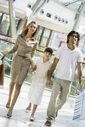 Family walking in mall holding hands and smiling (selective focus) - stock photo