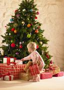 Little girl with parcels round christmas tree Stock Photos