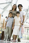 Family standing in mall smiling (selective focus) - stock photo