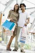 Couple standing in mall smiling (selective focus) - stock photo
