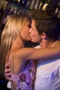Young couple kissing in a bar - stock photo