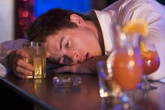 Drunk young man passed out in bar - stock photo