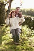 Stock Photo of couple with country garden swing