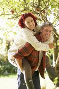 couple picking apples off tree - stock photo