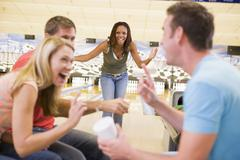 Woman bowling with friends Stock Photos