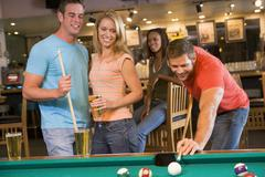 Friends playing pool - stock photo