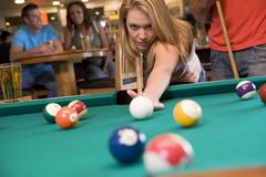 Woman playing pool - stock photo