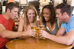 Two couples having beer together Stock Photos