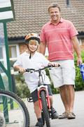 Father and Son outside school with bicycle - stock photo