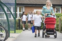 Woman and young boy pushing a stroller outside school with students in Stock Photos