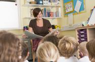 Stock Photo of Teacher in class reading with students in foreground (selective focus)
