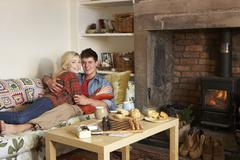 Stock Photo of young couple relaxing by fire
