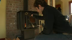 Man puts firewood into woodstove Stock Footage