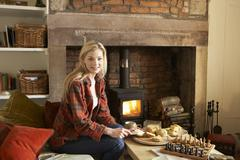 Stock Photo of young woman having tea by fire
