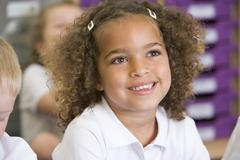 Student in class sitting on floor with students in background (selective focus) - stock photo
