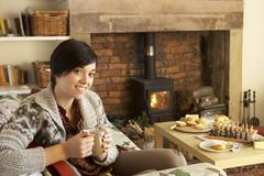 young woman having tea by fire - stock photo