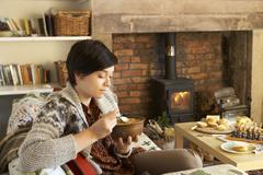 Young woman having tea by fire Stock Photos