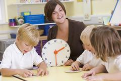 Students in class learning how to tell time (selective focus) Stock Photos
