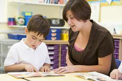 Student in class with teacher reading - stock photo