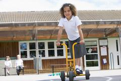 Student outside school on tricycle scooter - stock photo