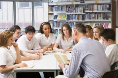 Students and teacher in a study group collaborating - stock photo