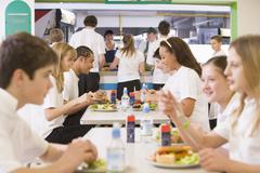 Students having lunch in dining hall Stock Photos