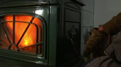 Gloved hands add  wood to Woodstove of Stock Footage