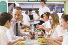 Students and teacher having lunch in dining hall Stock Photos