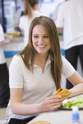Student having lunch in dining hall - stock photo