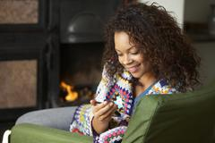 Stock Photo of young woman sitting by fire with phone
