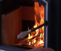 Hand closes glass door on wood stove with fire Stock Footage