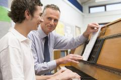 Male student learning piano with teacher in classroom - stock photo