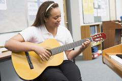 Female student learning guitar in classroom - stock photo