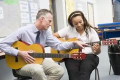 Female student receiving guitar lesson from teacher in classroom - stock photo