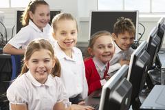 Lapset käyttävät tietokoneita koululuokassa Kuvituskuvat