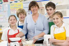 Students preparing ingredients in cooking class with teacher Stock Photos