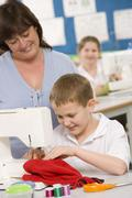 Male student using sewing machine with teacher - stock photo