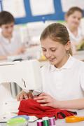 Female student using sewing machine - stock photo