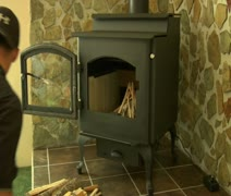 Man with baseball cap Starts fire in wood stove Stock Footage