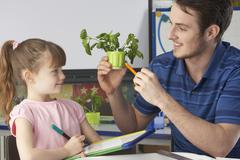Girl learning about plants with teacher Stock Photos