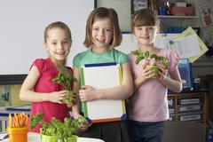 girls learning about plants in school class - stock photo