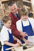 Male students reviewing woodworking plans with teacher - stock photo