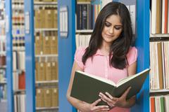 Woman in library reading book (depth of field) - stock photo