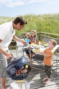 Family on vacation having barbecue Stock Photos