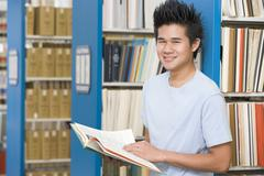 Man in library holding book (depth of field) Stock Photos