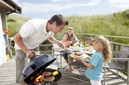 Stock Photo of family on vacation having barbecue