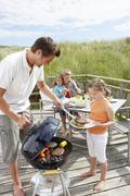 family on vacation having barbecue - stock photo