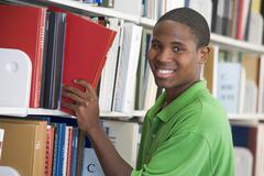 Man in library pulling book off a shelf (depth of field) Stock Photos