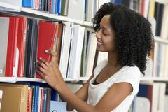 Woman in library pulling book off a shelf (depth of field) - stock photo