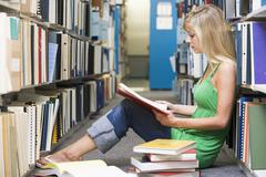 Woman sitting on floor in library reading book - stock photo